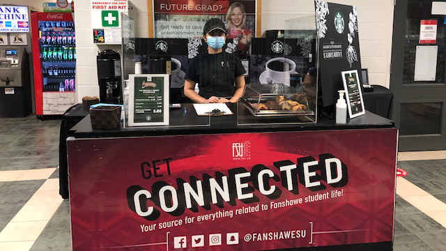 FSU employee standing behind Oasis Express coffee cart with FSU Connected branding